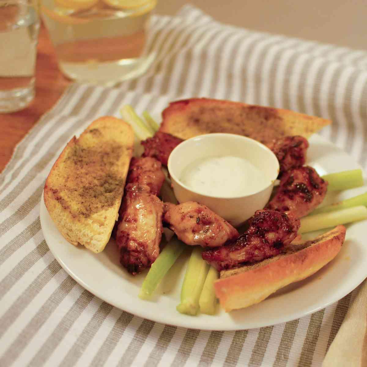 Pikantní medové kuřecí paličky, dip z nivy, rozpečená česneková bagetka, řapíkatý celer